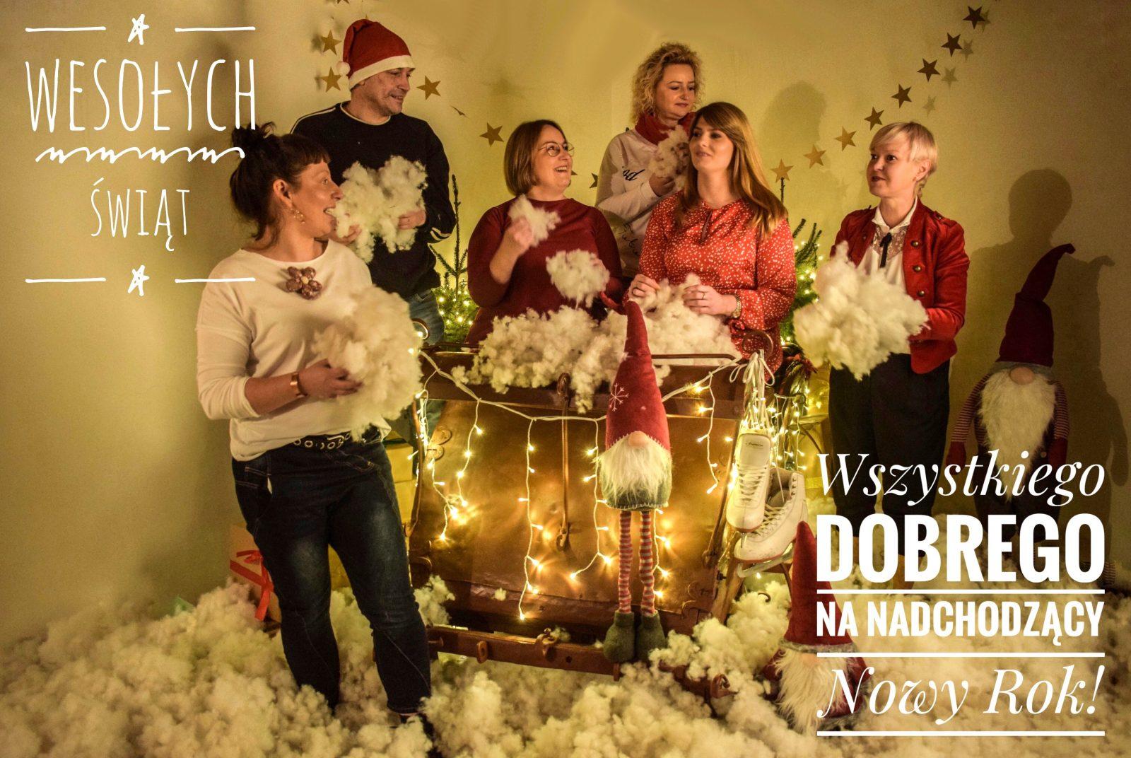Grafika. Wśród świątecznej dekoracji, sanie Mikołaja, skrzaty, lamki, sztuczny śnieg znajduje się grupa osób, pracownicy MDK. W prawym górnym rogu napis Wesołych Świąt. W lewym dolnym rogu napis Wszystkiego dobrego na nadchodzący nowy rok.